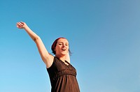 young happy woman with arms wide open representing freedom concept