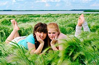 two girls lie on the bank of lake