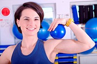 .young woman in fitness studio smiling and holding small pilates