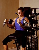 A young man BA young man BODY BUILDS using WEIGHT TRAINING EQUIPMENT _ MODEL RELEASED