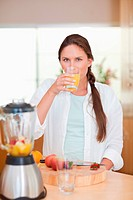 Portrait of a cute woman drinking fresh fruits juice
