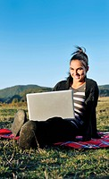 young teen woman work on laptop computer outdoor in nature with blue sky and green grass in background