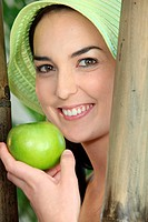 Woman smiling with green hat and apple