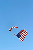 Sky diver carrying american flad with american flag parachute