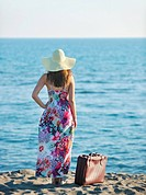 woman with suitcase travel bag on the beach representing exotic and luxury escape and freedom