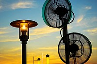 Thailand, Pattaya, Royal Garden Plaza, roof top, street lamp and fans against sunset sky