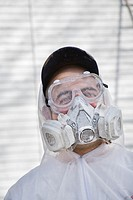Painter wearing a respirator, goggles, hat, and protective clothing