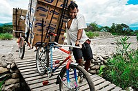 A Colombian smuggler pushing his bicycle fully loaded with contraband on an illegal foot bridge across the river Táchira on the Colombian-Venezuelan b...