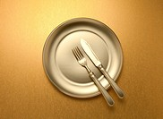 Knife and fork on a golden plate