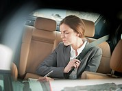 Businesswoman writing in backseat of car