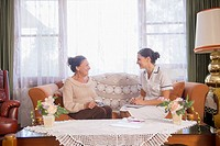 Hispanic nurse talking to senior woman