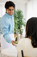 Mixed race waiter serving woman salad