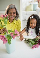 African American grandmother and granddaughter arranging flowers