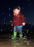 Girl splashing in puddle at night