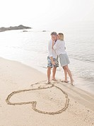 Couple drawing heart in sand on beach