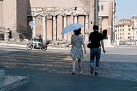 Europe, Italy, Rome  Young Roman couple walks towards ancient columns built into newer construction near the Teatro di Marcello Theatre of Marcellus