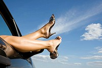 Woman´s legs and feet wearing silver high heeled shoes sticking out of car window