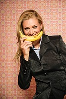 Germany, Stuttgart, Businesswoman with banana, smiling, portrait