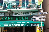Cafe with faulty neon sign and town sign posts in Lourdes, Hautes Pyrenees, France