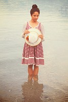 woman with vintage hat and dress standing in water