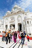 India. Punjab. Amritsar. The Golden Temple. The Parikrama Marble Path where Sikh believers pray, and the Ghanta Ghar Deohdi Gate of Victorian style.
