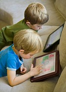 Two young children using digital tablets