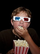 Boy watching a 3_D movie eating popcorn