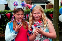 Young Teenage Girls Holding Cupcakes Decorated With Telephone Box, Post Box And Double Decker Bus For The Queen´s Diamond Jubilee Surrey England