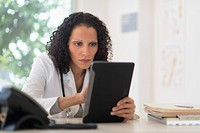 Portrait of doctor sitting in office and using digital tablet