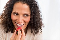 Portrait of woman eating strawberries