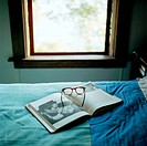 Eyeglasses and Open Book on Bed
