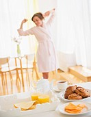 Breakfast scene with woman in white robe stretching