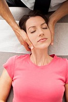 Woman laying down getting neck adjusted by chiropractor