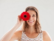 Beautiful woman holding flower in front of one eye