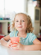 Portrait of girl drinking through straw