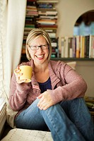 Woman holds a yellow mug in one hand and wraps the other hand around her knees. Woman is looking at the camera and laughing. Woman is wearing glasses.