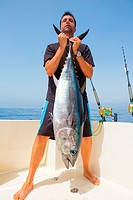 big Bluefin tuna catch by fisherman on boat trolling posing on deck