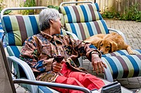 A woman relaxes with a dog on the deck in her backyard, Ontario, Canada