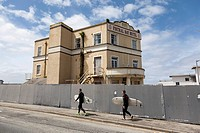 Surfers walking in front of the abandoned Fistral Bay Hotel, Newquay, Cornwall, England, Great Britain, Europe