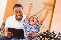 Mixed Race Father and Son Using Touch Pad Computer