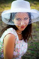 Sensual woman in the summer season with hat in a park