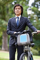 Young businessman with bicycle standing at park