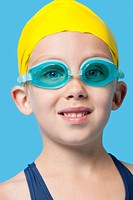 Close_up portrait of a happy young girl wearing swim cap and goggles over blue background
