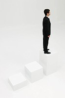 Businessman standing on highest step