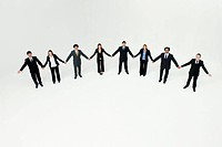 Businessmen and businesswomen standing together holding hands