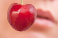A sweet cherry in front of a face