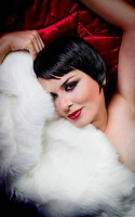 seminude beautiful short haired brunette woman lying on red silk with white fur