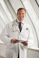 Caucasian doctor using digital tablet in hospital corridor