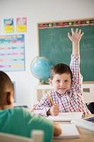 Caucasian boy raising hand in classroom