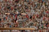 Hispanic gymnast in mid_air over balance beam